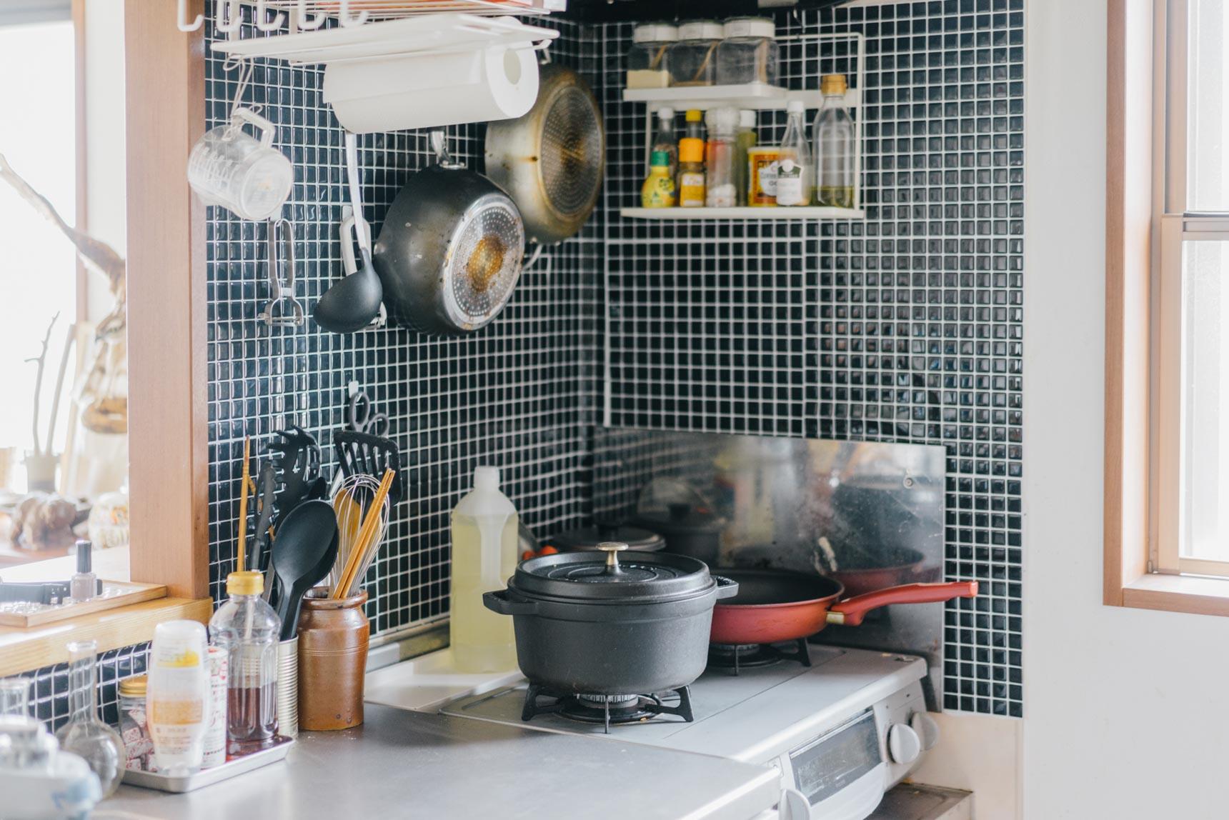 換気扇フードに様々なフックやラックをつけて、キッチンツールを収納。壁には剥がせるタイルシートを貼りました。