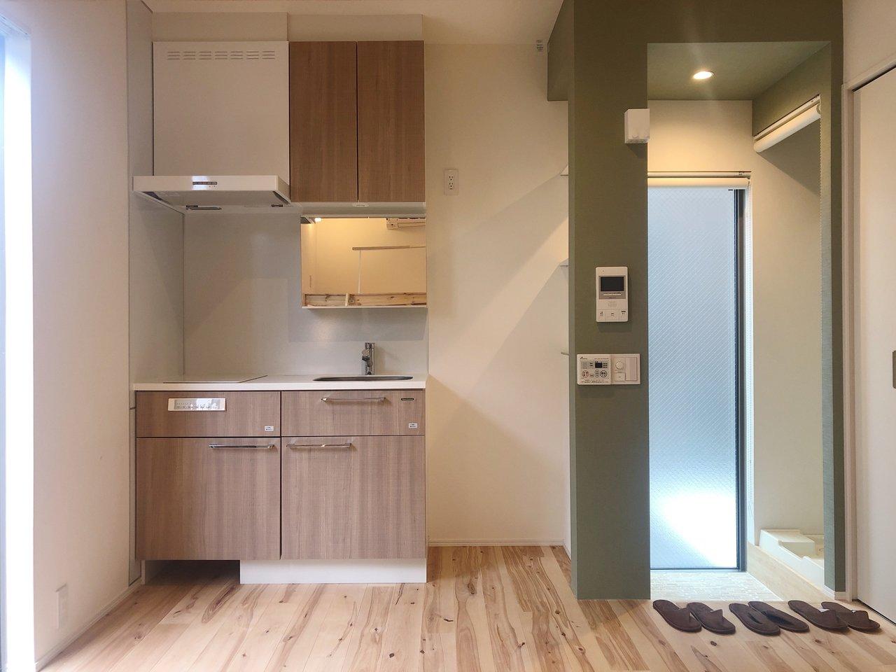 キッチンは二口コンロ。作業スペースもありますね。玄関周りのモスグリーンの壁紙が、床とマッチしておしゃれ!