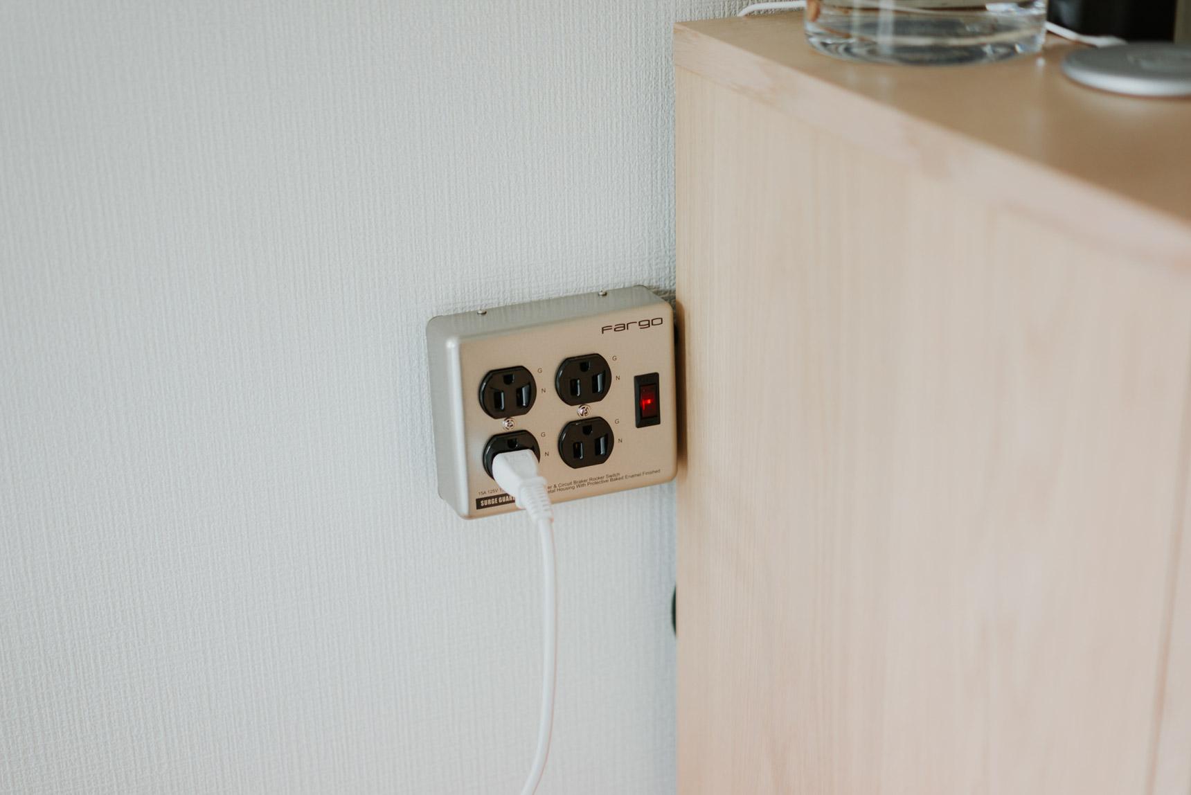 コンセントが家具の裏側にあたるため、電源タップをちょうどいい位置に壁掛け。