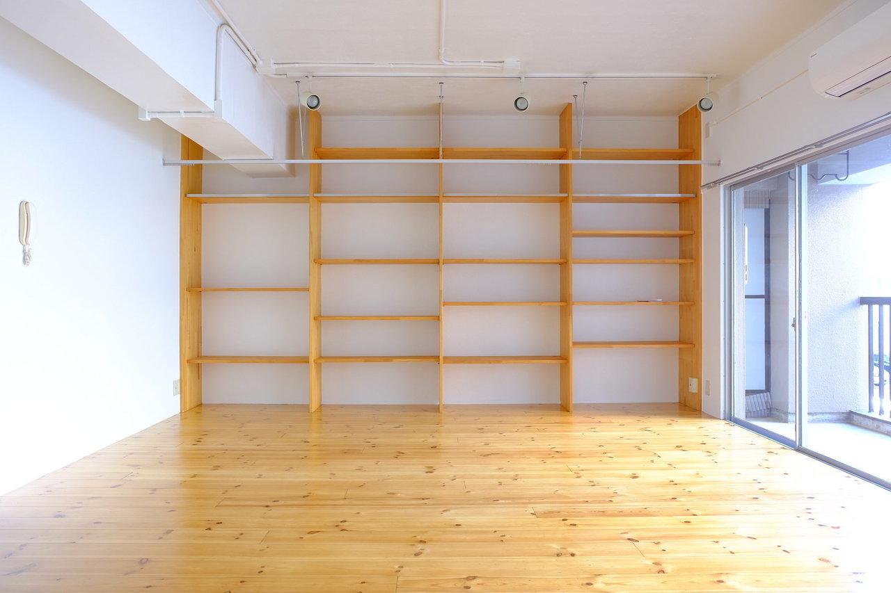 この部屋の驚きは2つ。まずはこの壁一面の棚!収納スペースがない分、ここに洋服も、本も、趣味のものも、全部きれいに並べてしまいましょう。見せたくない場所にはところどころおしゃれな布をかければ、アシンメトリーな感じで、個性が出ていいですね。