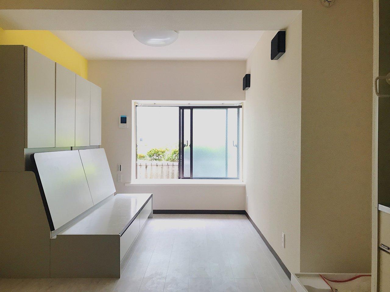 大きなクローク付きのソファベッドがあるお部屋です。黄色のアクセントクロスが実に爽やかです。木目調の浴室の壁もポイント!