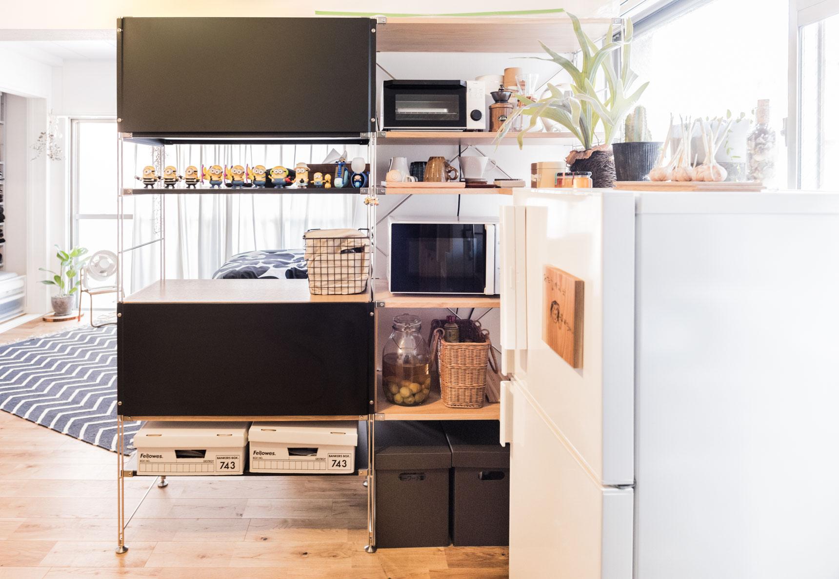 背板をうまく組み合わせることで、ベッドルーム側から見ると本棚、キッチン側から見ると家電や食材の棚と、2つの機能を持たせています。