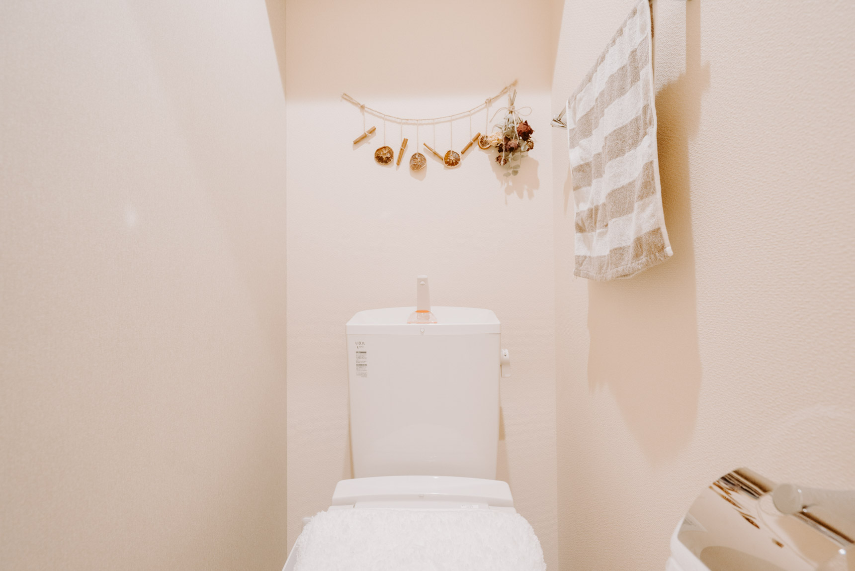 トイレには楽しいドライフラワーの飾りを。こちらも色味の抑えられた落ち着く雰囲気。