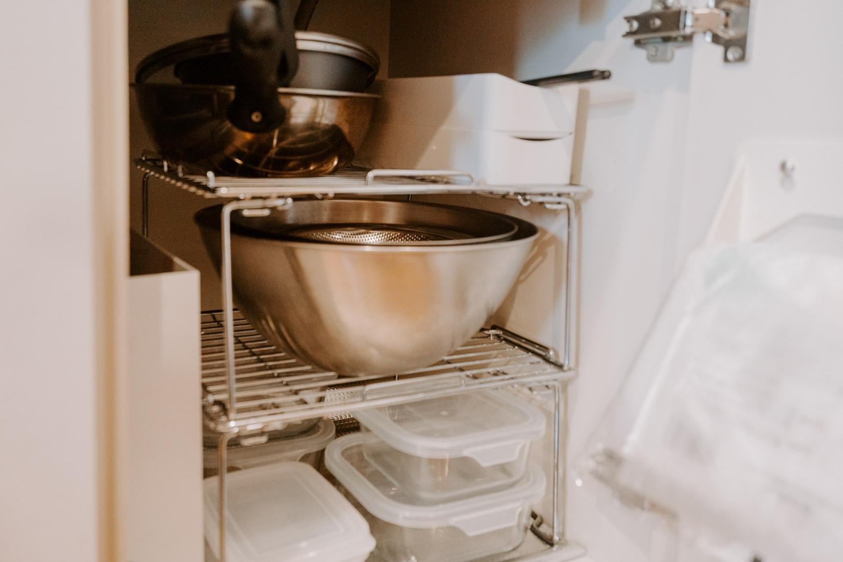 小さなシンク下の収納は、ニトリのキッチンラックを使って整頓。100円ショップのプラスチックのものと比べると、ステンレスで重いものを載せても安心感。