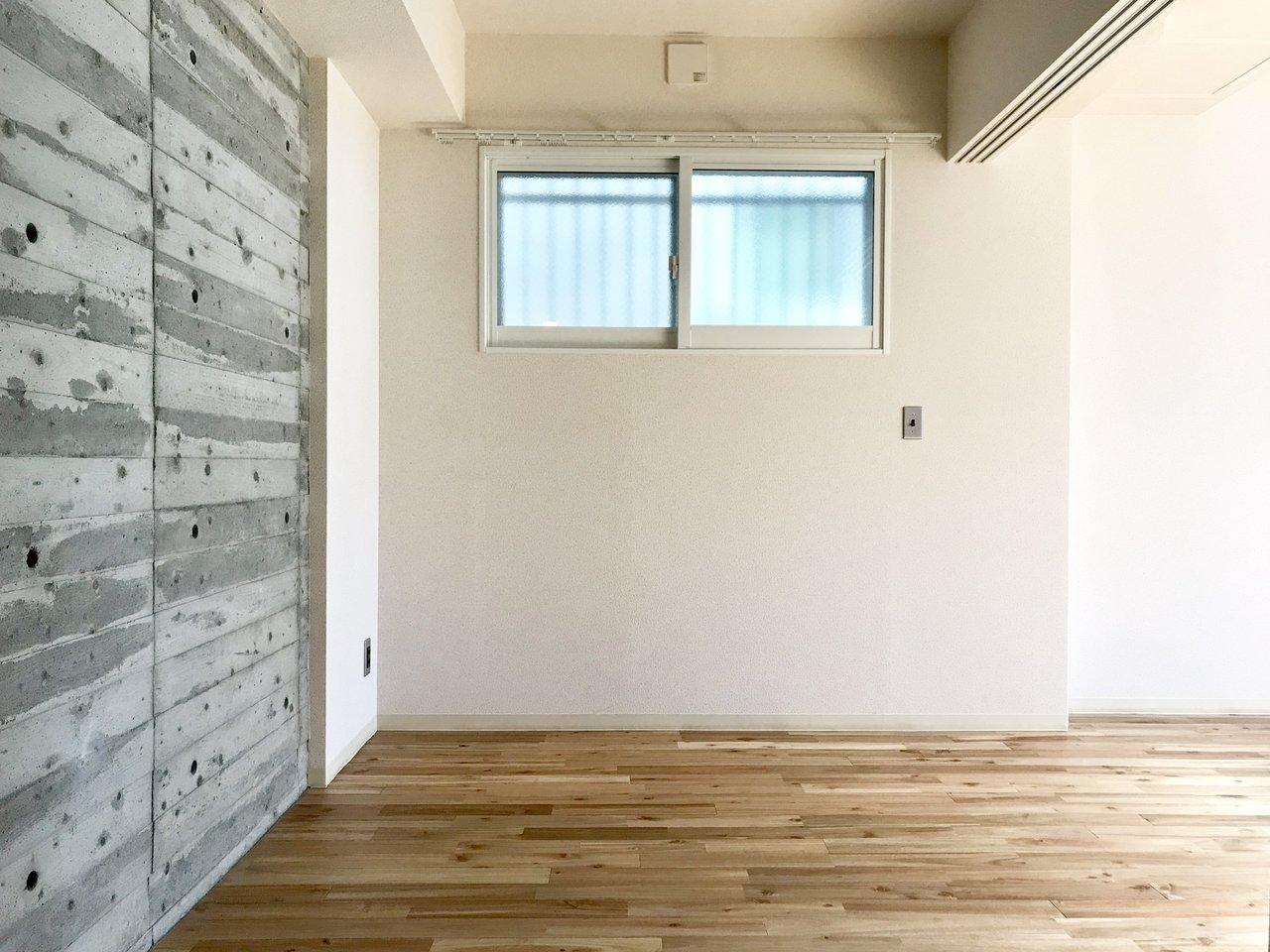 隣の洋室の壁紙もコンクリート&木目風のおしゃれなものを採用。部屋全体に統一感があ っていいですね。天井も少し高めです。窓も高い位置にあるので、窓際にインテリアを配置するのも可能ですね。