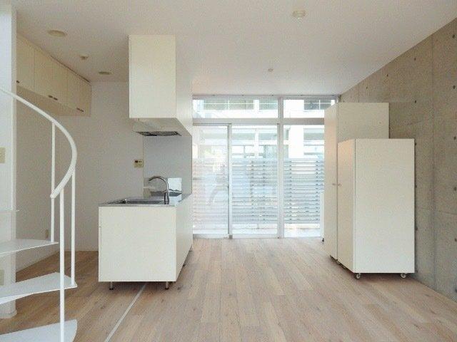ホワイトのキッチンや収納スペース、木目のフローリング、コンクリート素材の壁。様々な素材が一緒になって、ちゃんと調和している、そんなお部屋です。螺旋階段で2階に行くことも。賃貸物件で螺旋階段ってなかなかないですよ。