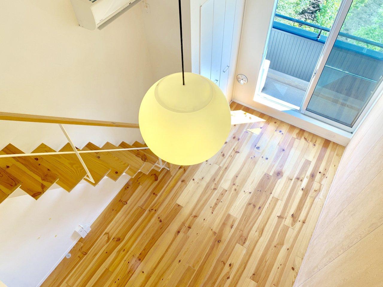 白が貴重のシンプルな内装で、無垢床の存在がより一層強調されている、ワンルームでロフト付きのお部屋。窓からは、心地よい風が入り込んでくるうえに、緑いっぱいで心癒されるんです。