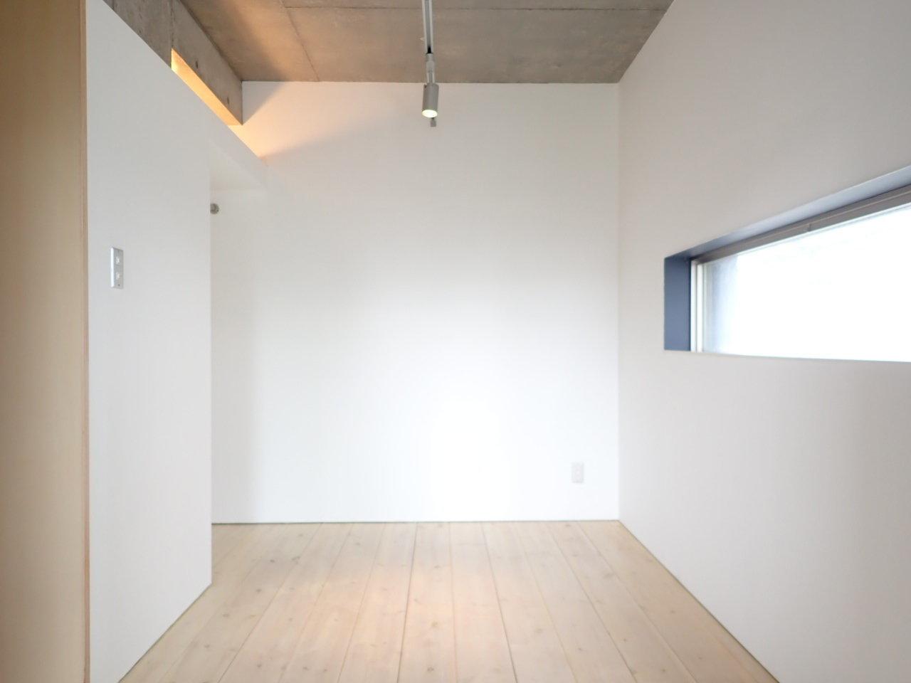 室内はこんな感じ。バルコニーへつながる大きな窓もありますが、もう1つ、細長い窓もついています。コンクリート打ちっ放しの感じと、床面の木の感じと。様々な素材があって、面白い。