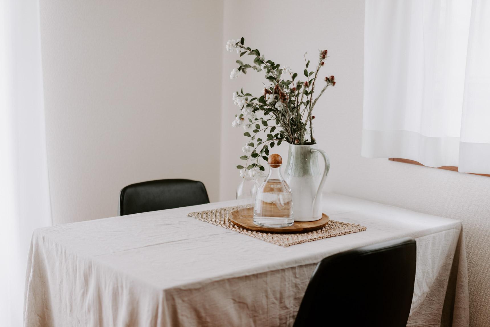 テーブルクロスをかけ、花を飾った素敵なダイニング。花瓶はWest Elm、カラフェはH&M HOMEのもの。