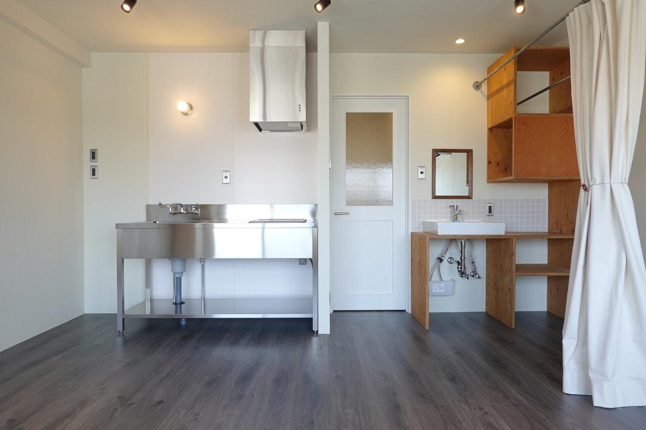 """洗面台の横には棚がたくさんあるので、タオルなどの収納に。ナチュラルな棚の色合いがいいですね。キッチンはステンレス。収納スペースはないので、キッチン下や壁際を使って、""""魅せる収納""""を心がけましょう。"""
