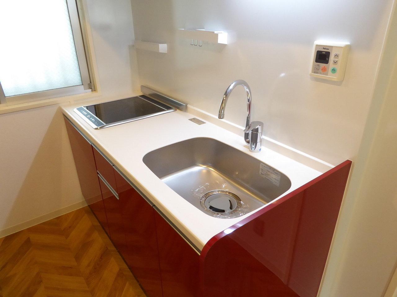 キッチンは収納スペースもしっかりある、IHコンロ型。自炊もしっかりできそう。蛇口もなかなか見ないタイプでおしゃれですよね。ナチュラルな雰囲気でありつつ、キッチンの赤でピリリと引き締まります。