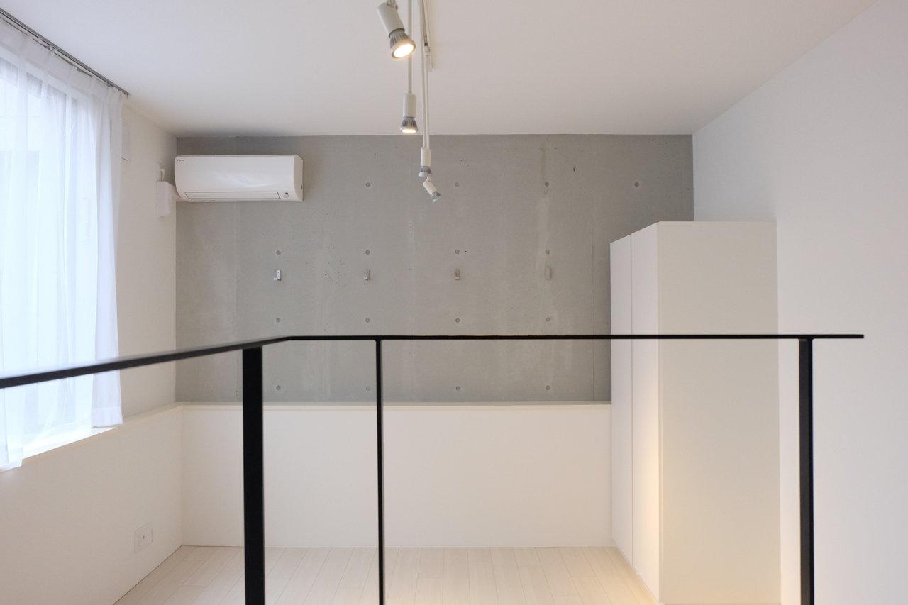 キッチン側から見ると、こんな感じ。ワンルームと言えど、キッチンとの間にステップがあるので、メリハリが出ます。コンクリート打ちっ放しの壁もかっこよさをプラス。