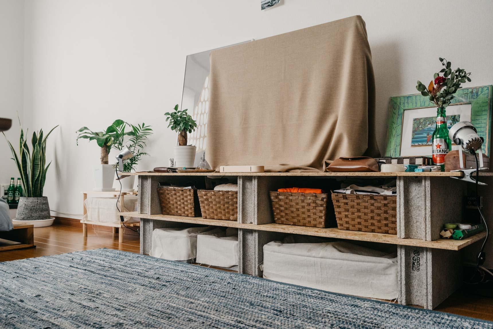 ホームセンターで手に入るブロックとボードを使って簡単DIY。テレビは布で隠し、中にしまうものも全てカゴや布で隠して生活感をなるべく感じさせないように。(このお部屋はこちら)