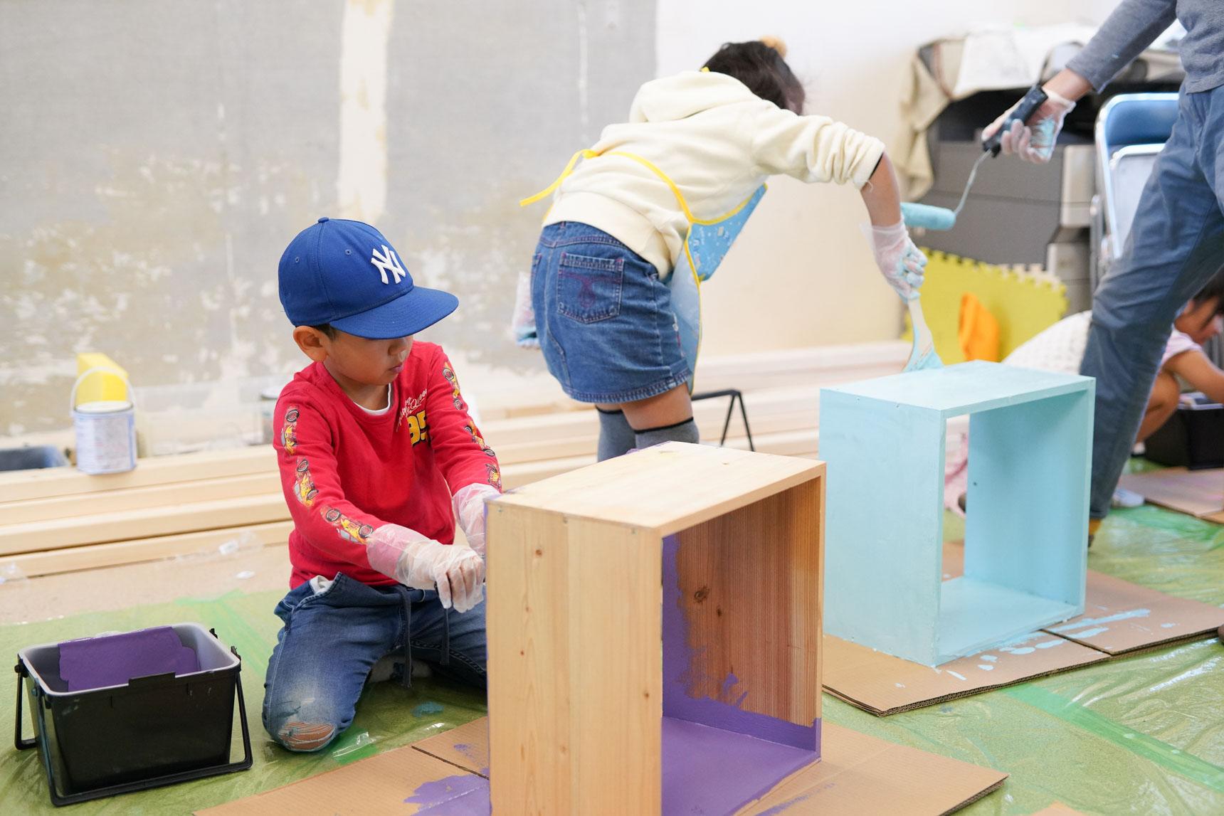 この日は、「本棚づくり」のワークショップが行われていました。4年前、としょかんのオープン当初に本を入れる木箱を作りました。この木箱に今度は色を塗ってリメイクします。団地に住むたくさんの子どもたちが参加し、大盛況。