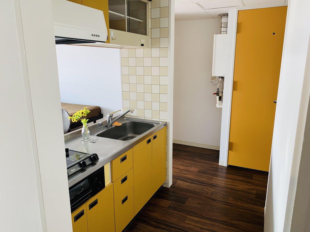 キッチンは黄色で明るいイメージを与えてくれて、スペースもかなり広々。壁面のタイルもかわいいですよね。背面にも棚が設置されているので、食器棚などに活用できそうです。(※家具はサンプルです)