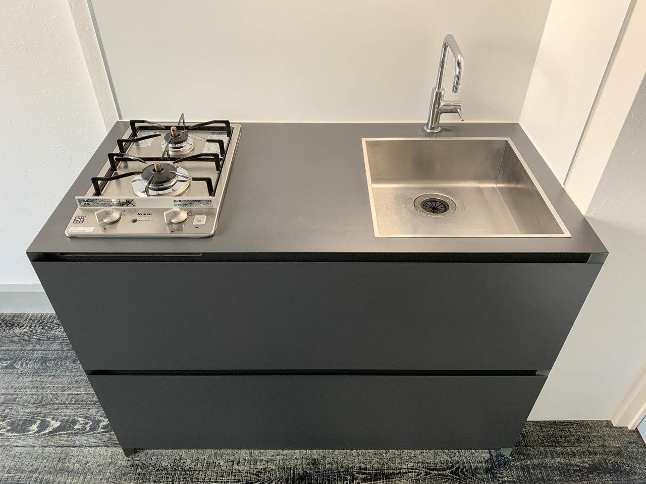 キッチンはコンパクトですがコンロが2口あるなど、自炊派にはうれしい設備。黒とグレーの間のような色で部屋全体をキリっと引き締めてくれています。引き出しの広さも十分で収納力もありますよ。