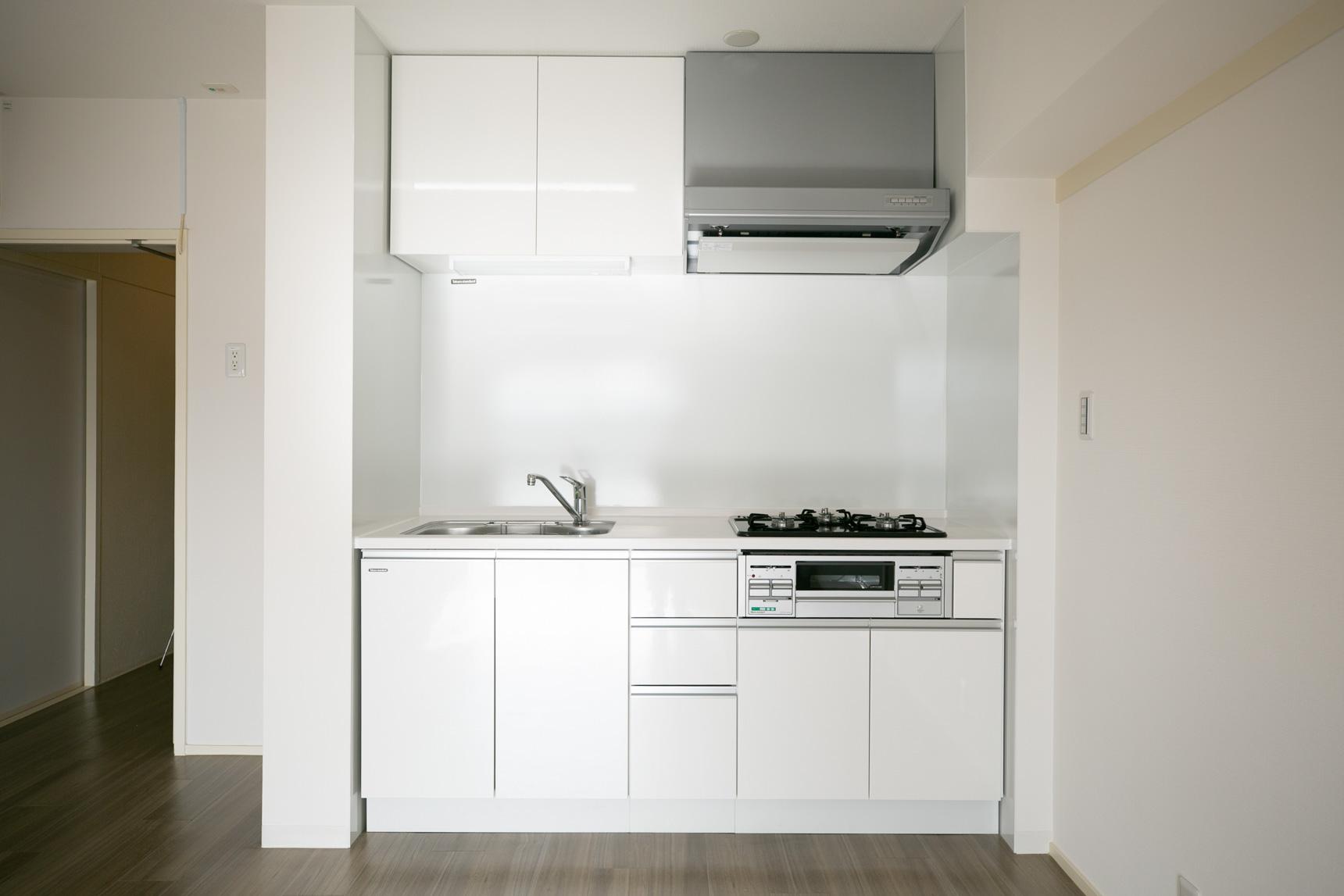真っ白の新しいシステムキッチン。正面の壁はホーローパネルになっているのでお手入れもしやすく、マグネットもつけられるのでフックなどで収納も増やせますよ。