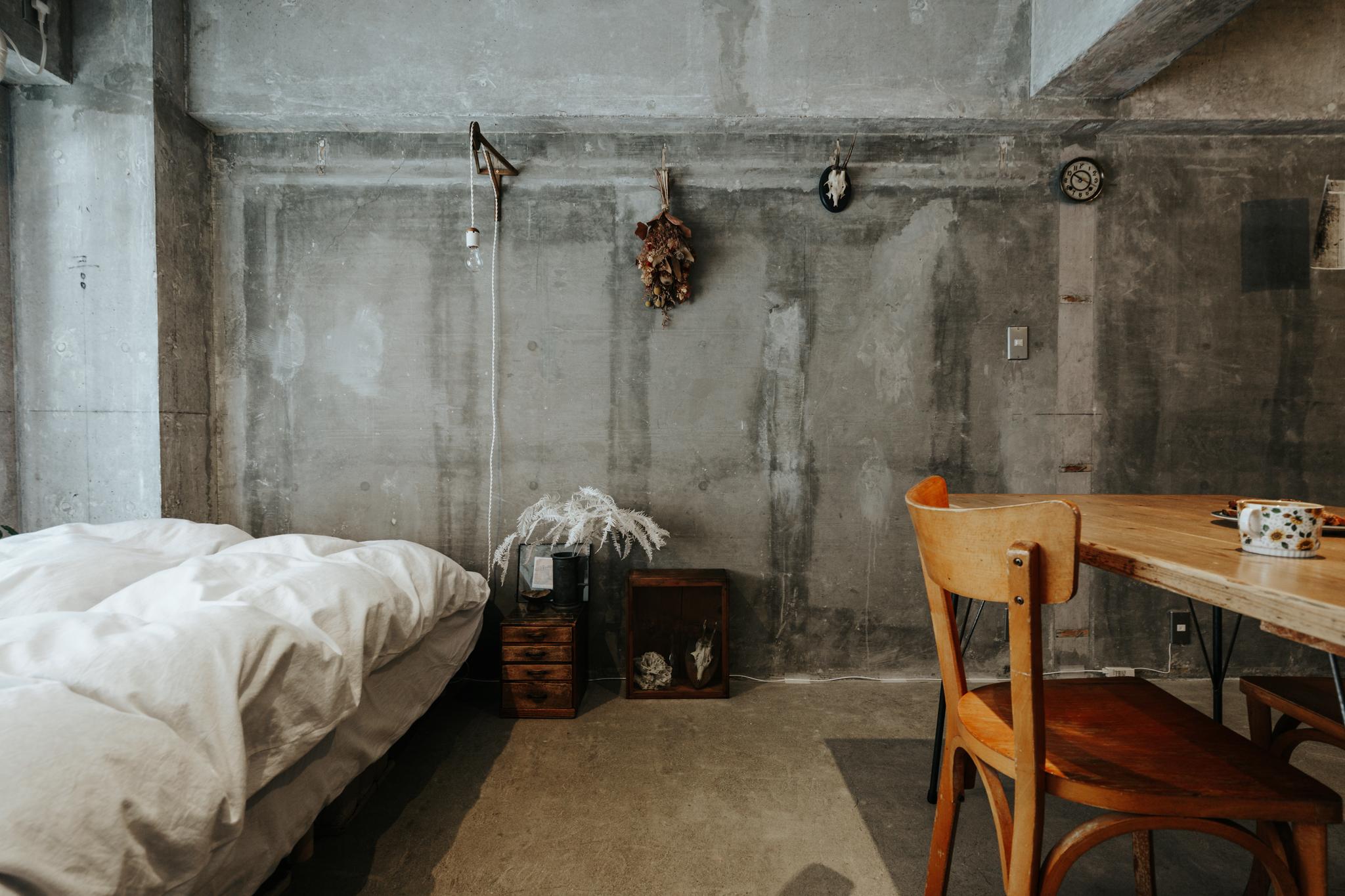 壁紙を剥いであらわれた、コンクリートの表面。ざっくりとした質感の壁に、蚤の市や骨董市で買ってきた雑貨や小さな家具が、よく映えます。