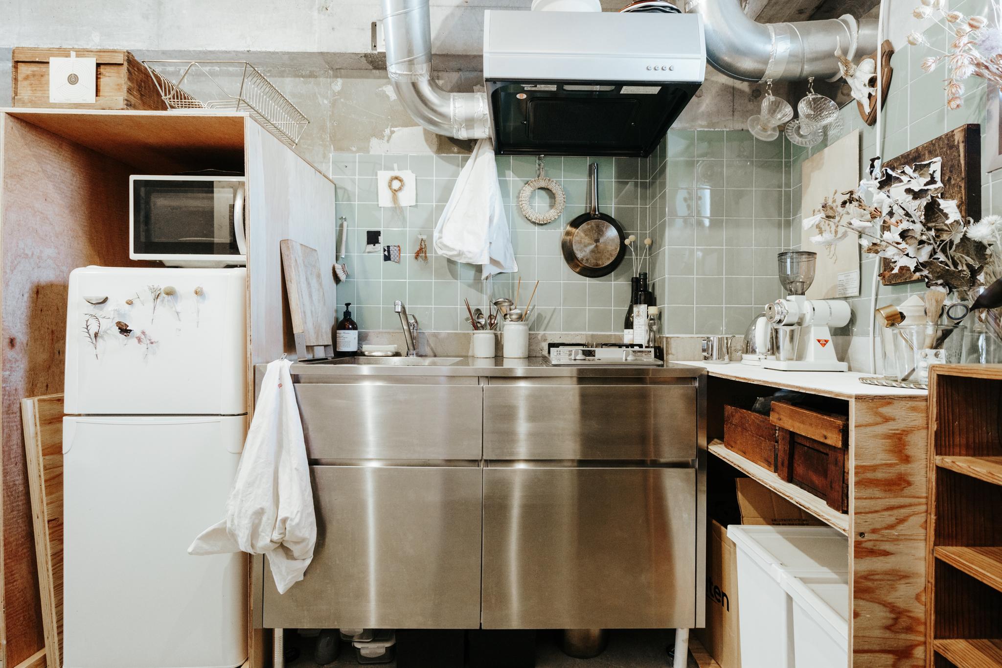 シンプルなステンレスキッチンの周りには、自分で木の板を使って作った作業台などを合わせています。