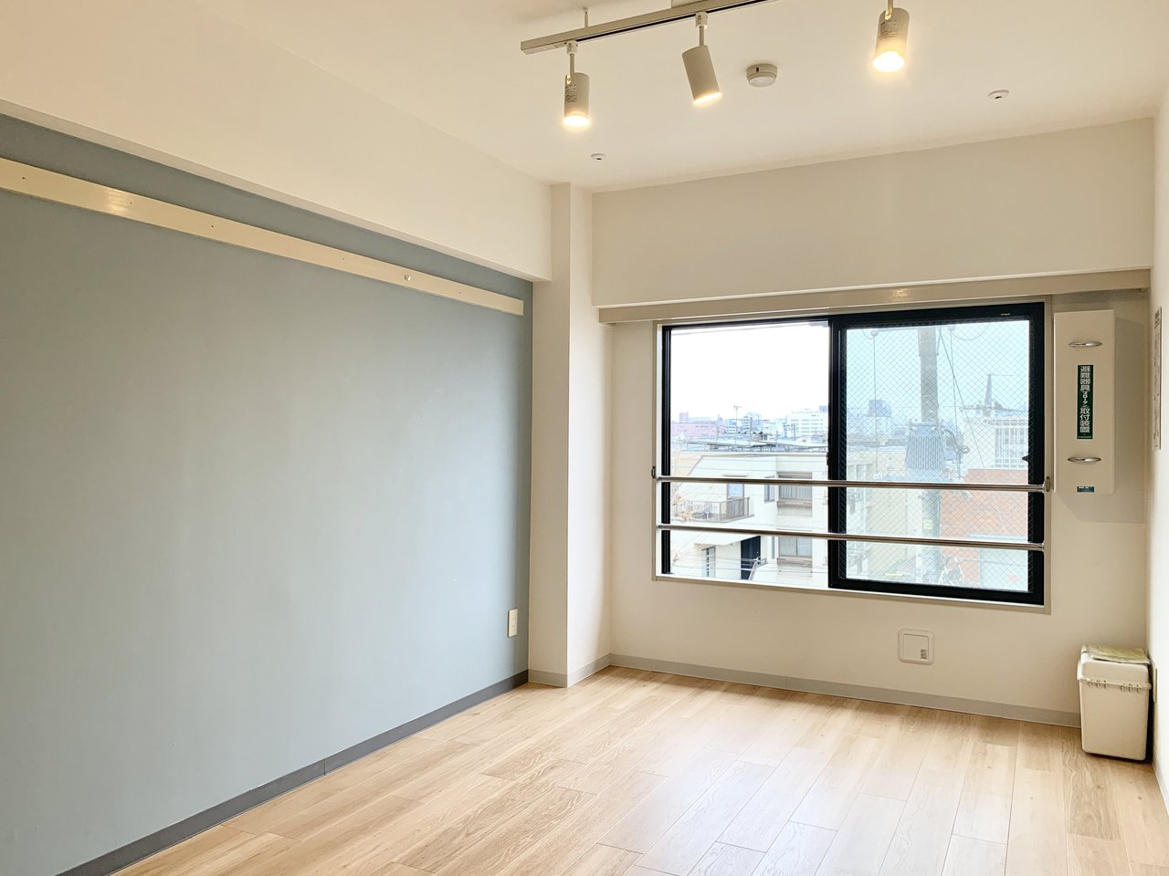 水色の壁紙が、お部屋の印象をさわやかに仕立ててくれる、ワンルームタイプのお部屋。淡い色合いのフローリングと、天井に備え付けられているライティングレールがさらにおしゃれに見せてくれます。