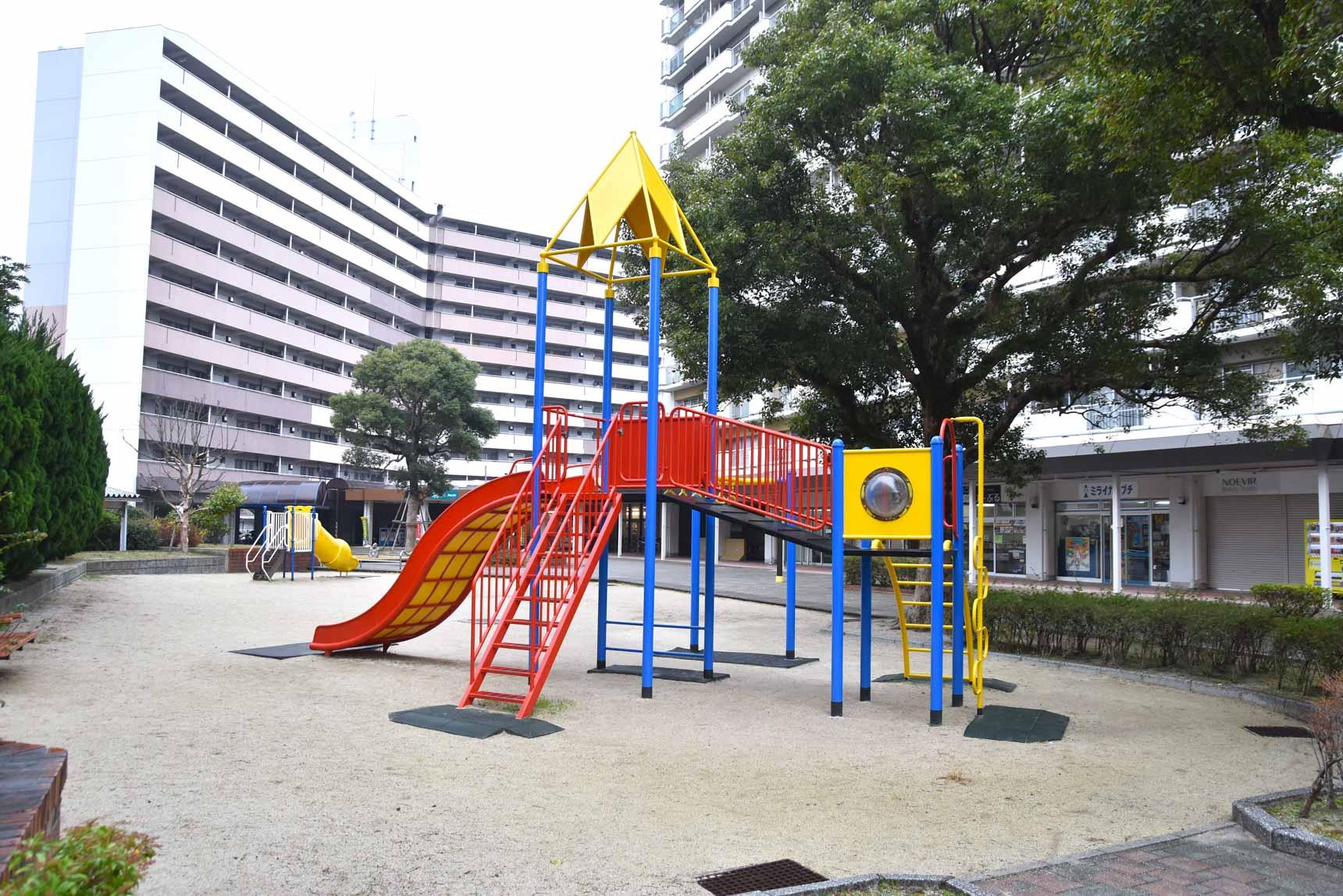 住棟の真ん中には遊具も備えた広場がある四箇田団地。住棟の1階はアーケード商店街で、クリニックや飲食店も入居しています。