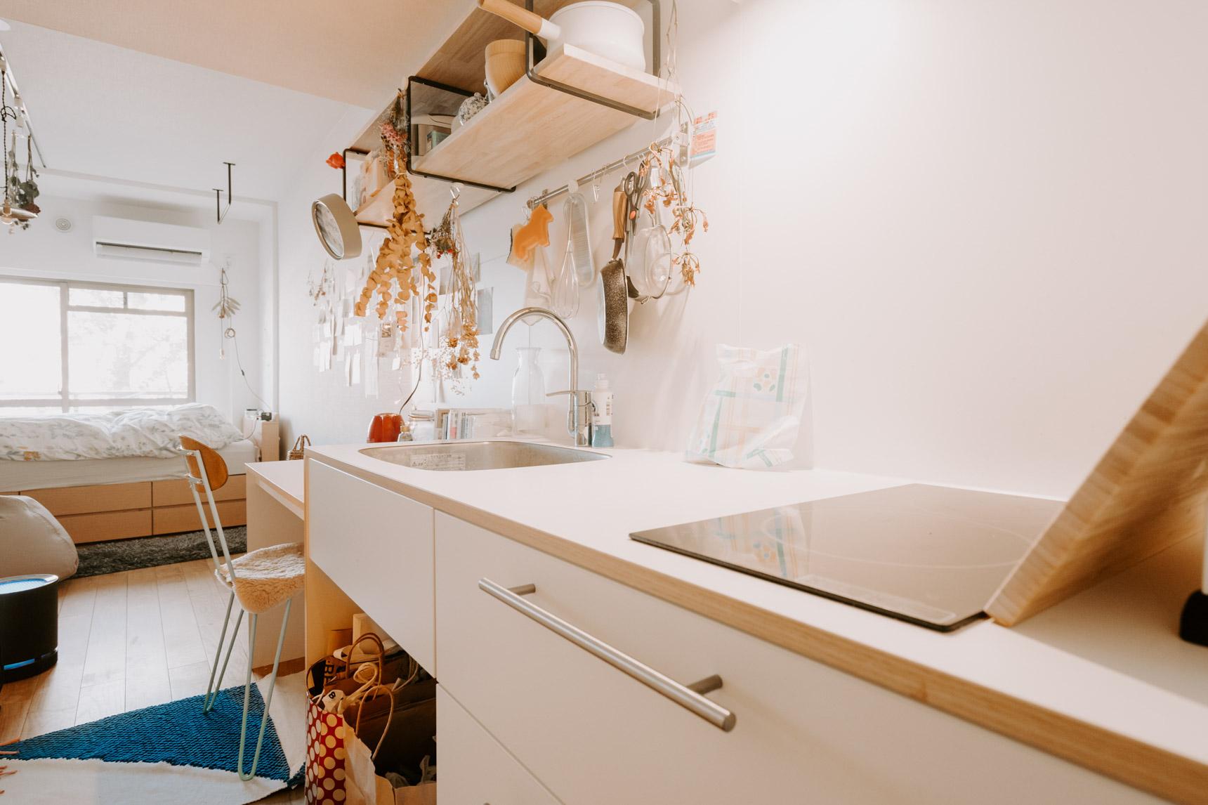 玄関を入ると、廊下に真っ白なキッチンとつくりつけのテーブルが並ぶ、特徴的な間取り。ここでご飯を食べたり、便利で気に入っているそう。