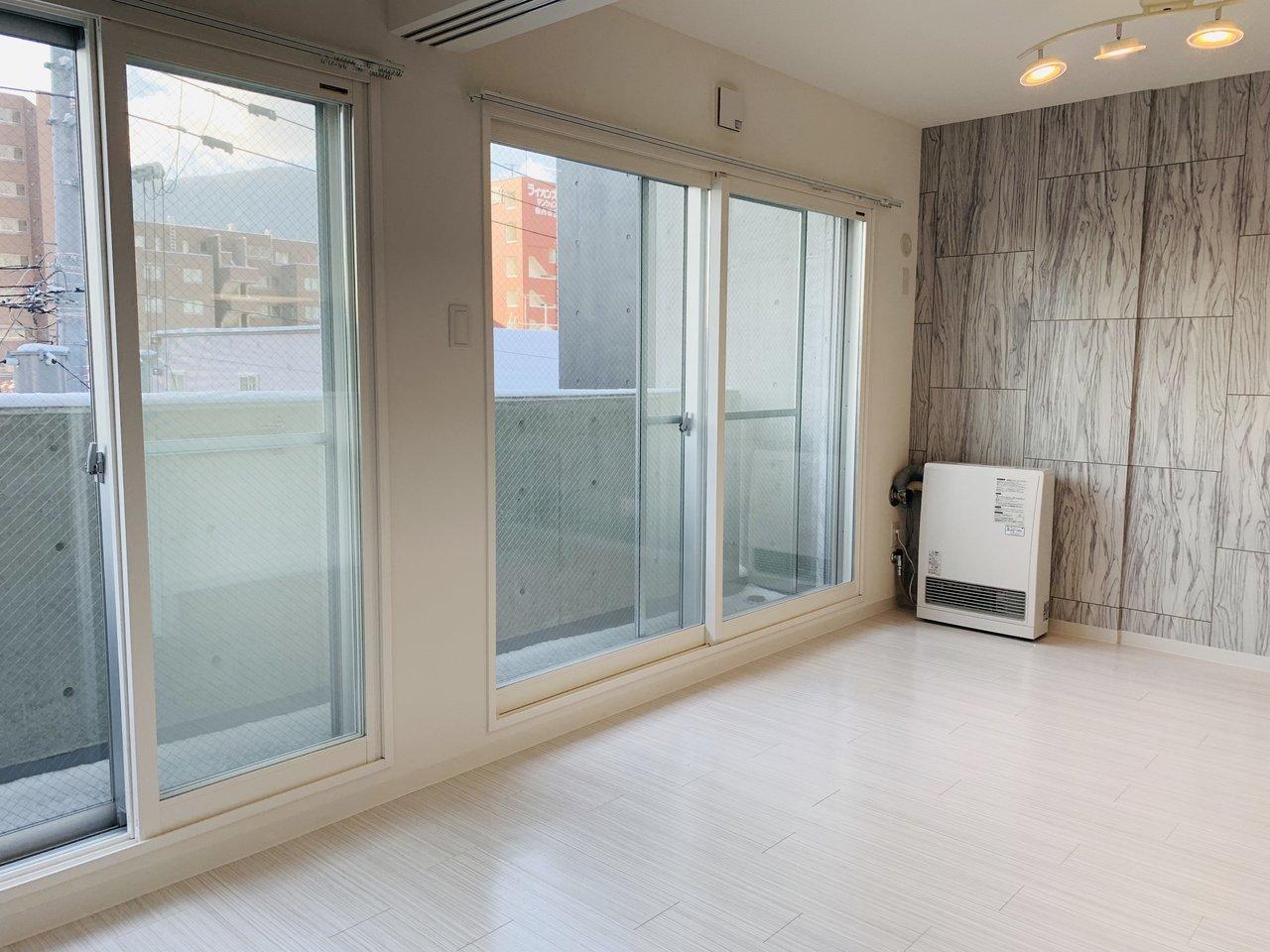 大きな南向きの窓が特徴の1LDKのお部屋。リビングは7畳ありますよ。グレーの木目調のアクセントクロスも、高級感があっていいですね。
