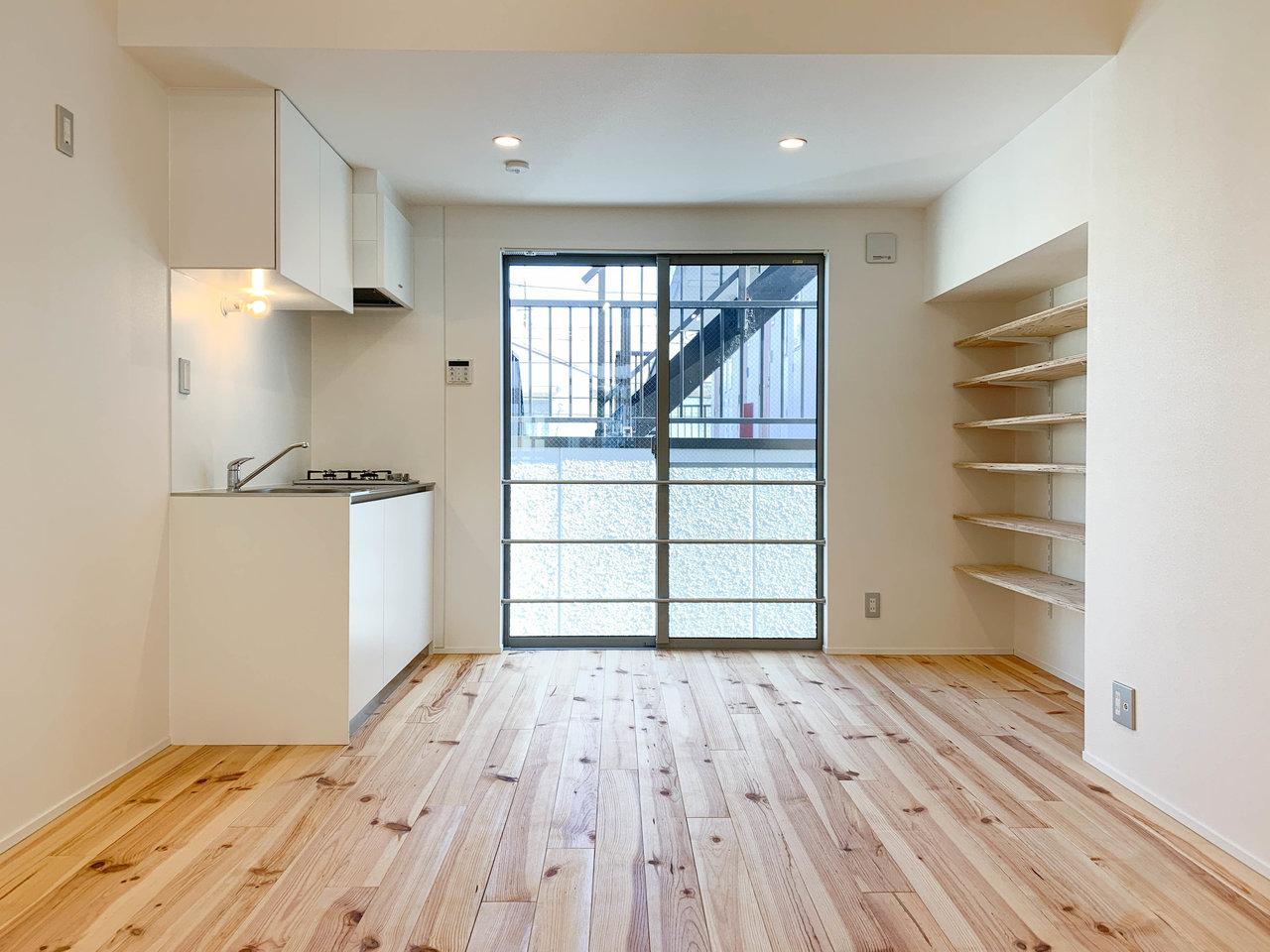 まずは2階のリビング。ロフトがある分天井がとても高いのが特徴です。壁に備え付けられた棚は本棚かな。キッチンも2口ガスコンロ付きの使いやすいタイプのものになっています。