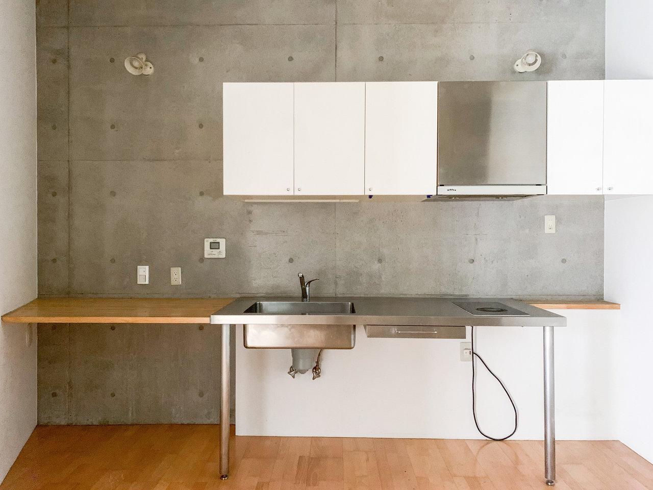 4件目はコンクリートの壁が印象的なこちらのお部屋。メゾネットタイプの1LDK物件です。キッチンはかっこよく、広々としています。左側の棚には、炊飯器やレンジなどを置けたらいいですね。