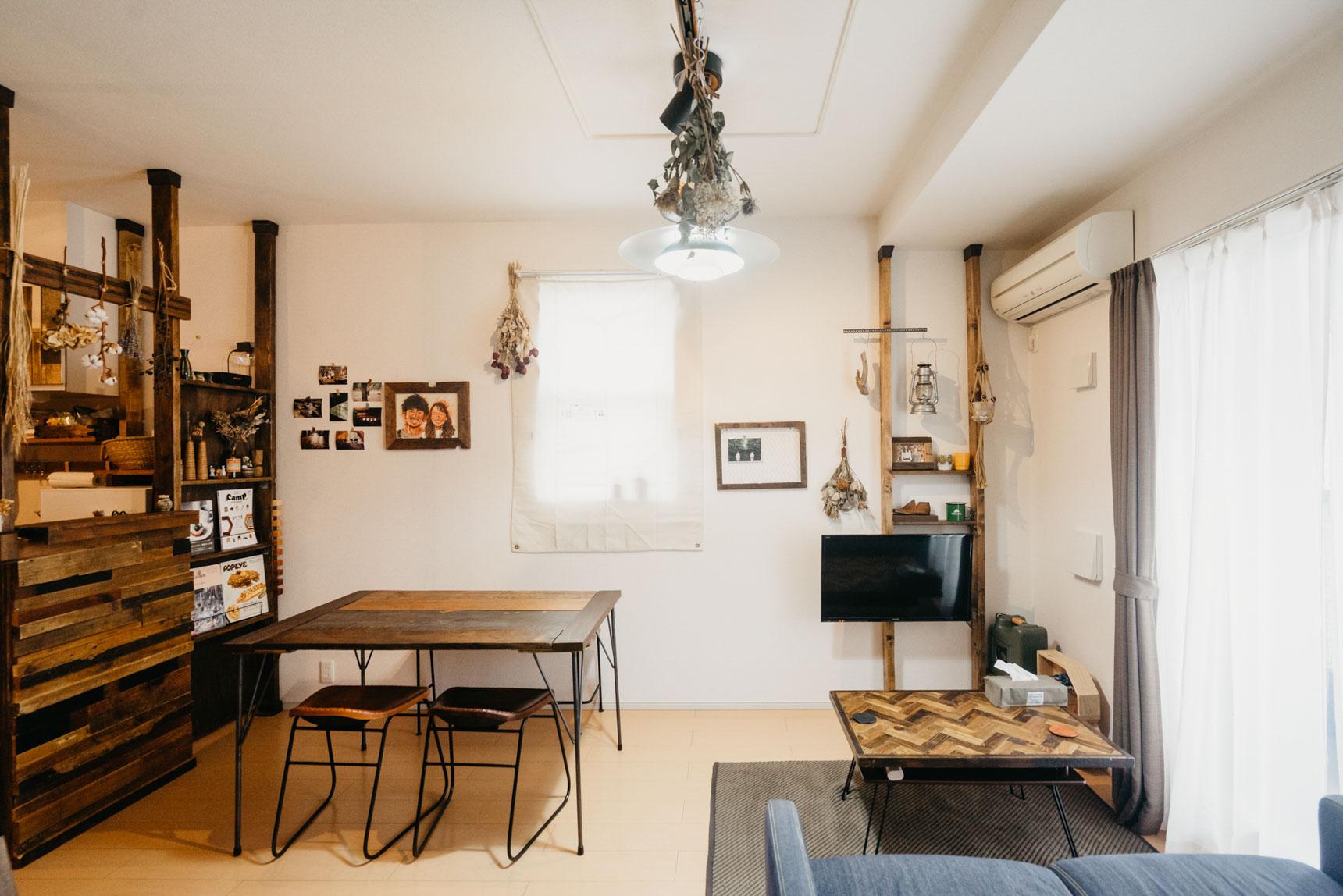 キッチンを含めて13畳ほどのLDKに、DIYのダイニングテーブル、ローテーブル、ソファを配置した例。
