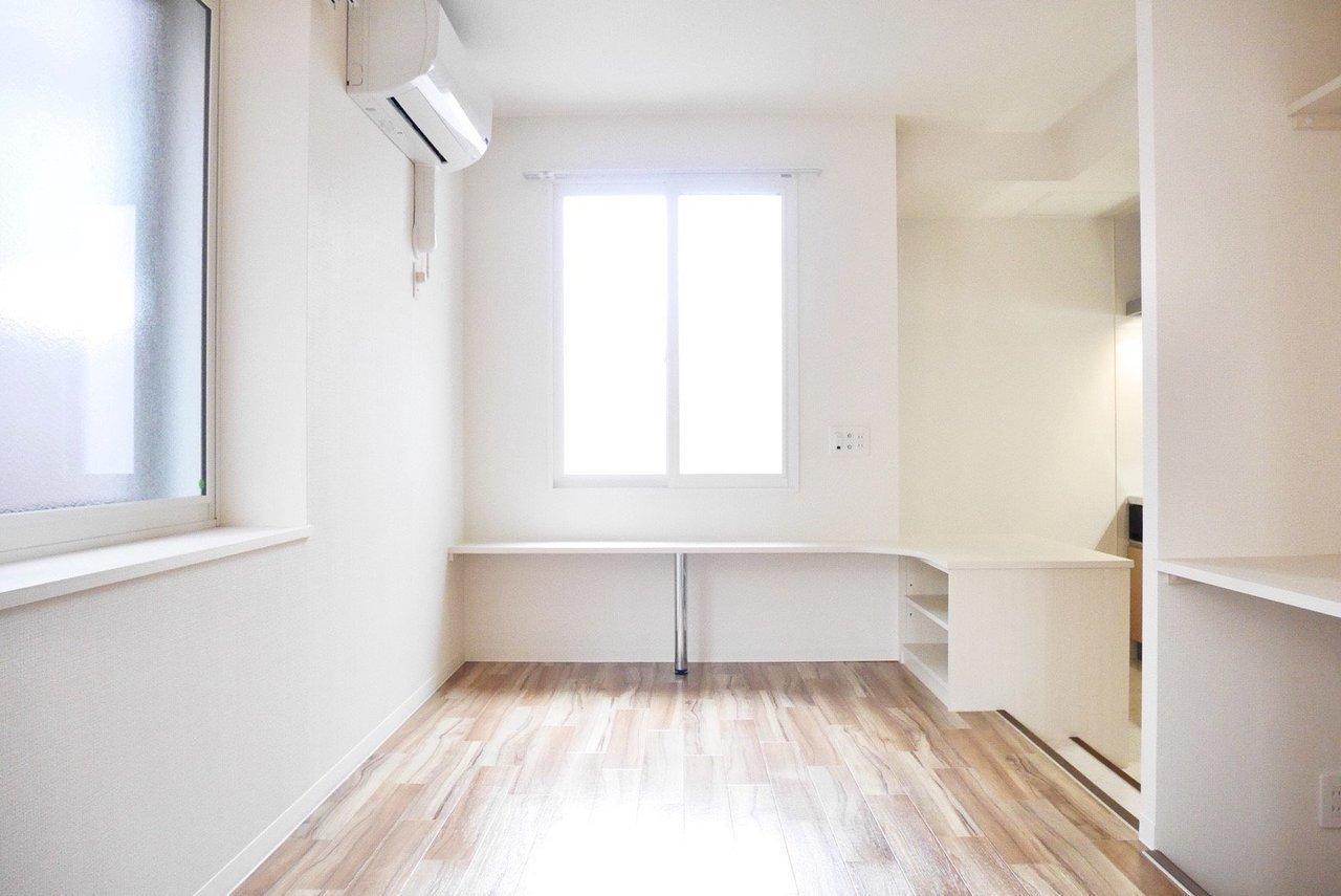 すっきりとした10.8畳の1Kのお部屋。壁沿いに棚が多くあるので、収納棚をあえて買わなくても大丈夫そう。光がたくさん降り注ぎます。