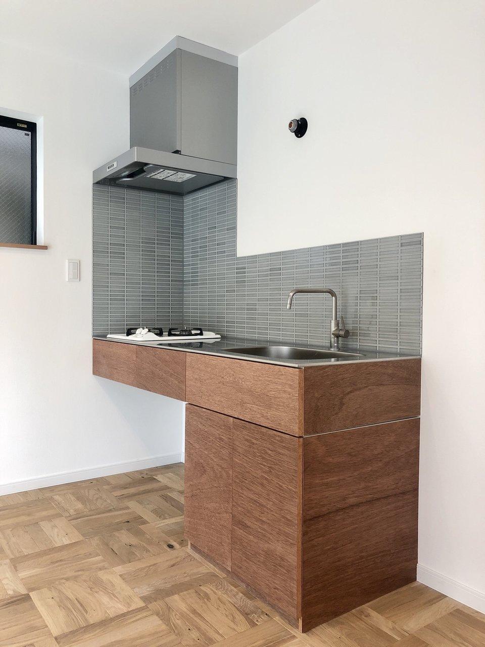 グレー&ブラウンの色調のキッチンは、とってもシンプルな造り。コンロ下にはスチールワゴンを置いて、調味料や鍋などの調理器具をしまう場所にしてはいかがでしょう。