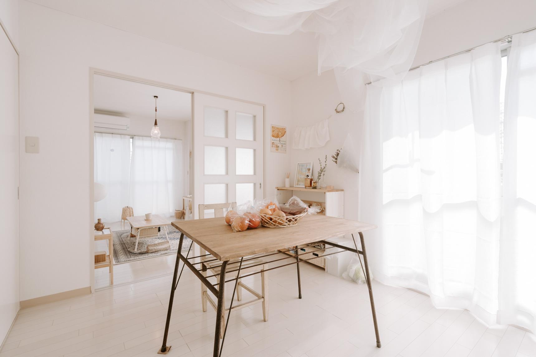 カーテンも同じ素材なので、統一感もありカフェのような明るい印象に。ダイニングテーブルと椅子はGIRAFFES CRAFTのもの。