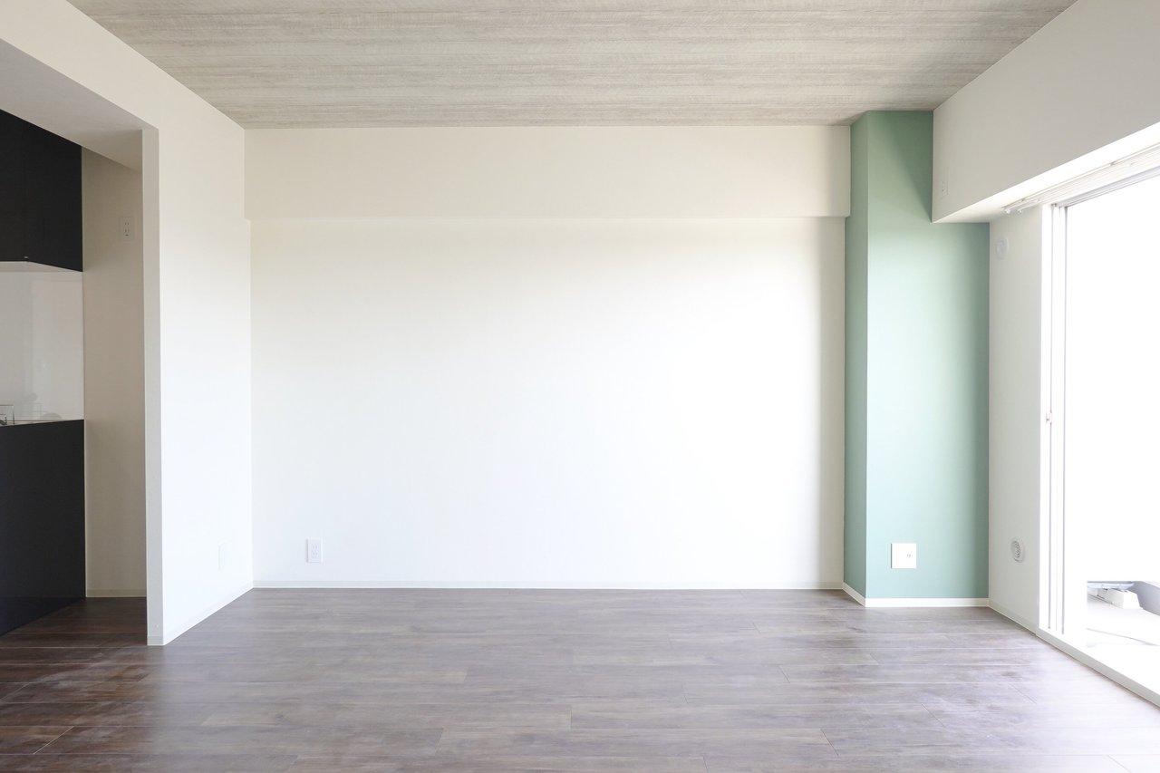 リビングはこちら。緑の鮮やかさも派手過ぎず、お部屋のいいアクセントになっていますね。天井の木目調も落ち着いた、あたたかい印象を与えてくれます。さらに窓からはたっぷりと陽射しが差し込んできます。
