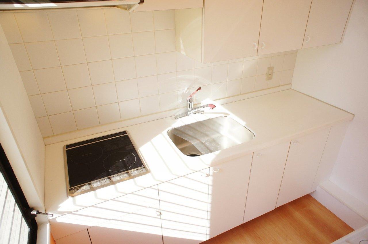 キッチンは白で統一されていて収納スペースも十分。シンクが真ん中にあるタイプって珍しいですね。