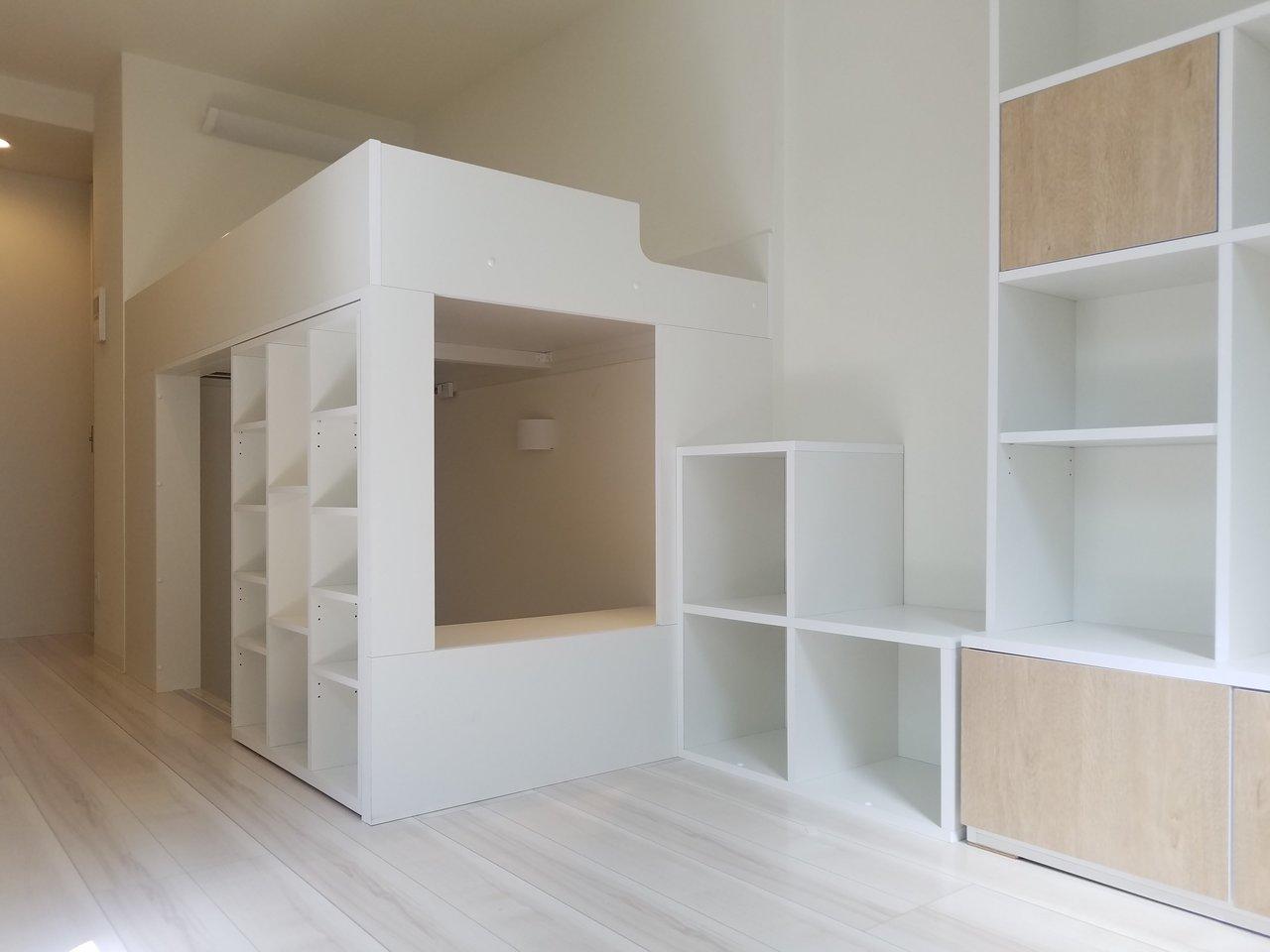 白系のフローリング、壁伝いにたくさん組まれた棚。ちょっと他では見ないような、変わったデザインのワンルームのお部屋です。リビングは8畳あって、ワークスペース、ロフトまであります。