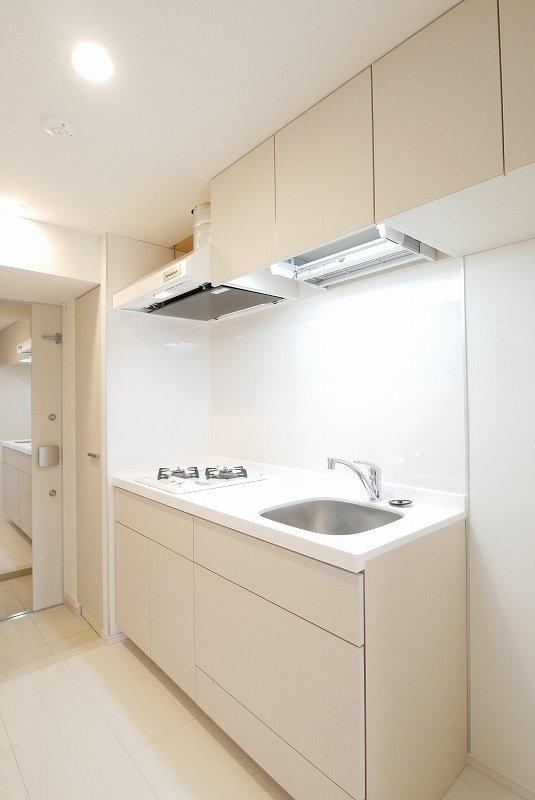 キッチンもご覧の通りの、白。シンクはややコンパクトですが、作業スペースや収納棚、二口コンロ、と使い勝手はかなり良さそう。