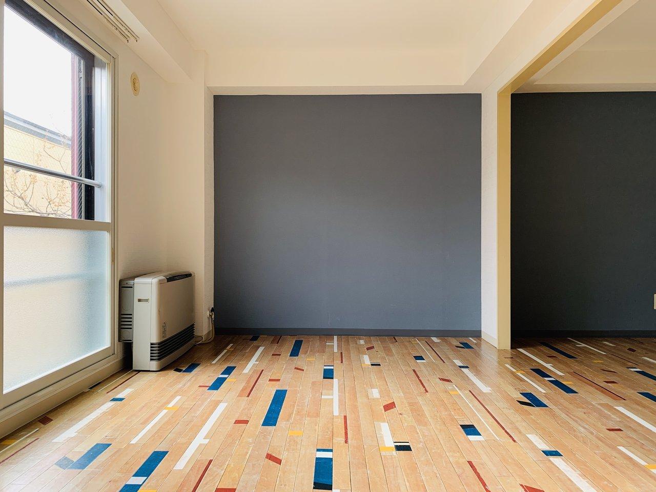 室内に入ってまず驚くのが、この床材。赤・青・白などのアクセントカラーがちりばめられていて、見た目にも明るい印象の1DKのお部屋です。その明るさを中和するかのような、落ち着いた色合いの壁紙もいいですね。