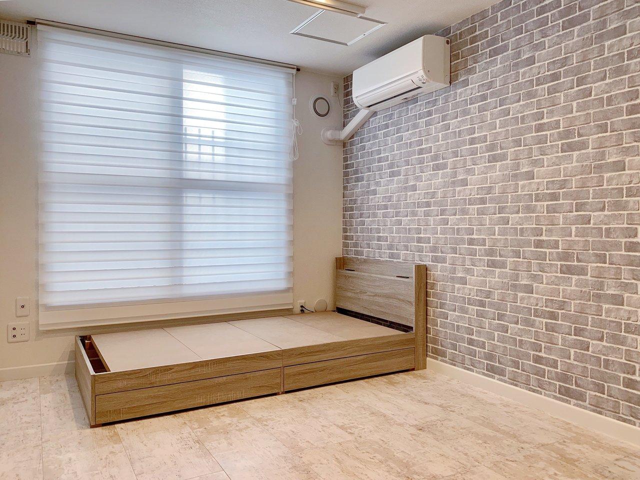 6畳のお部屋には、このようにベッドがどーんと。あ、マットレスもご準備くださいね。ベッド下はちょっとした収納スペースにもなっています。壁紙もレンガ調であたたかみがありますね。