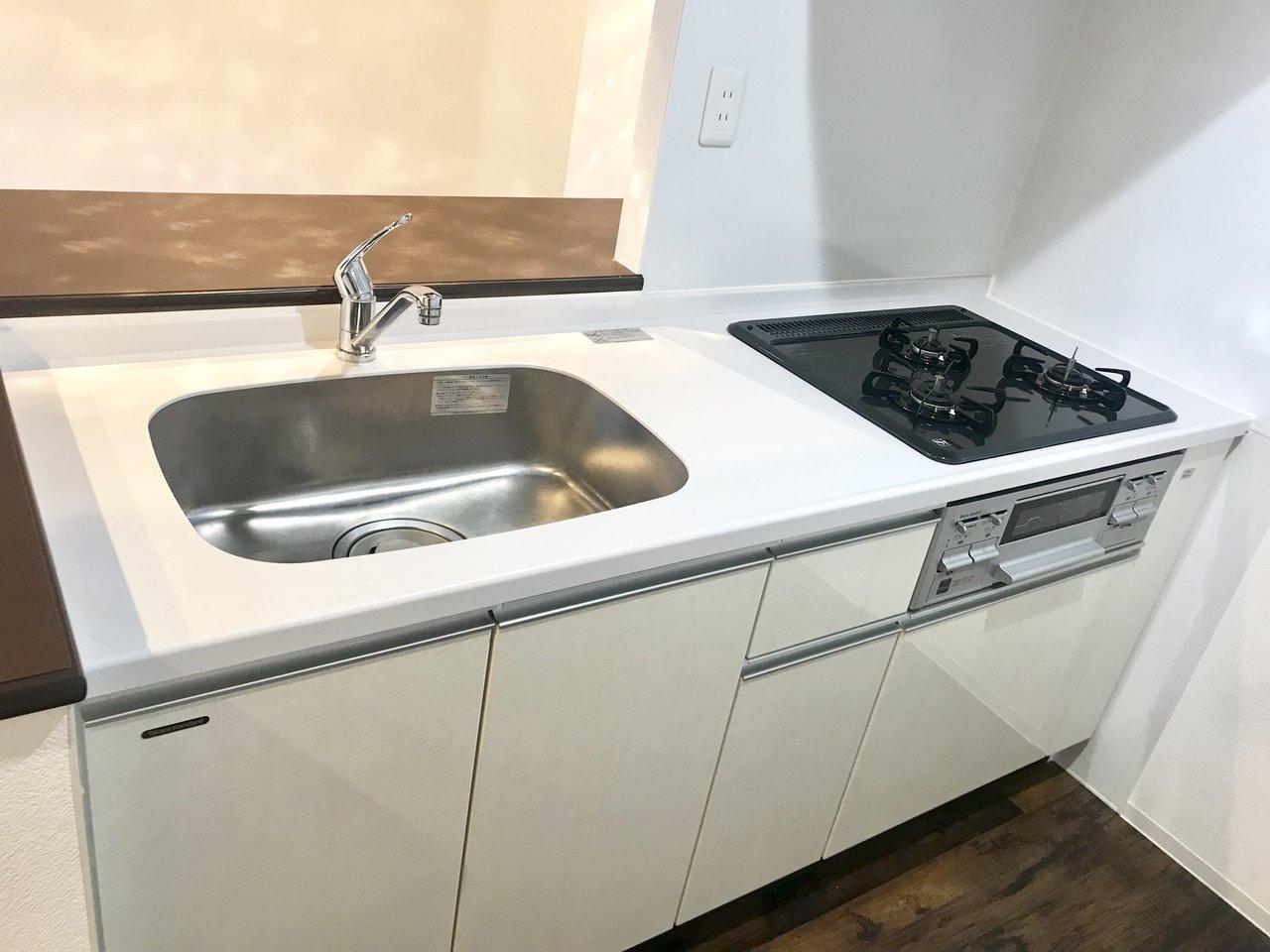 キッチンの中はこんな感じ。3口コンロに、グリル付き。さらに後ろを振り返ると、作業スペースと収納棚もあって、かなり便利です。
