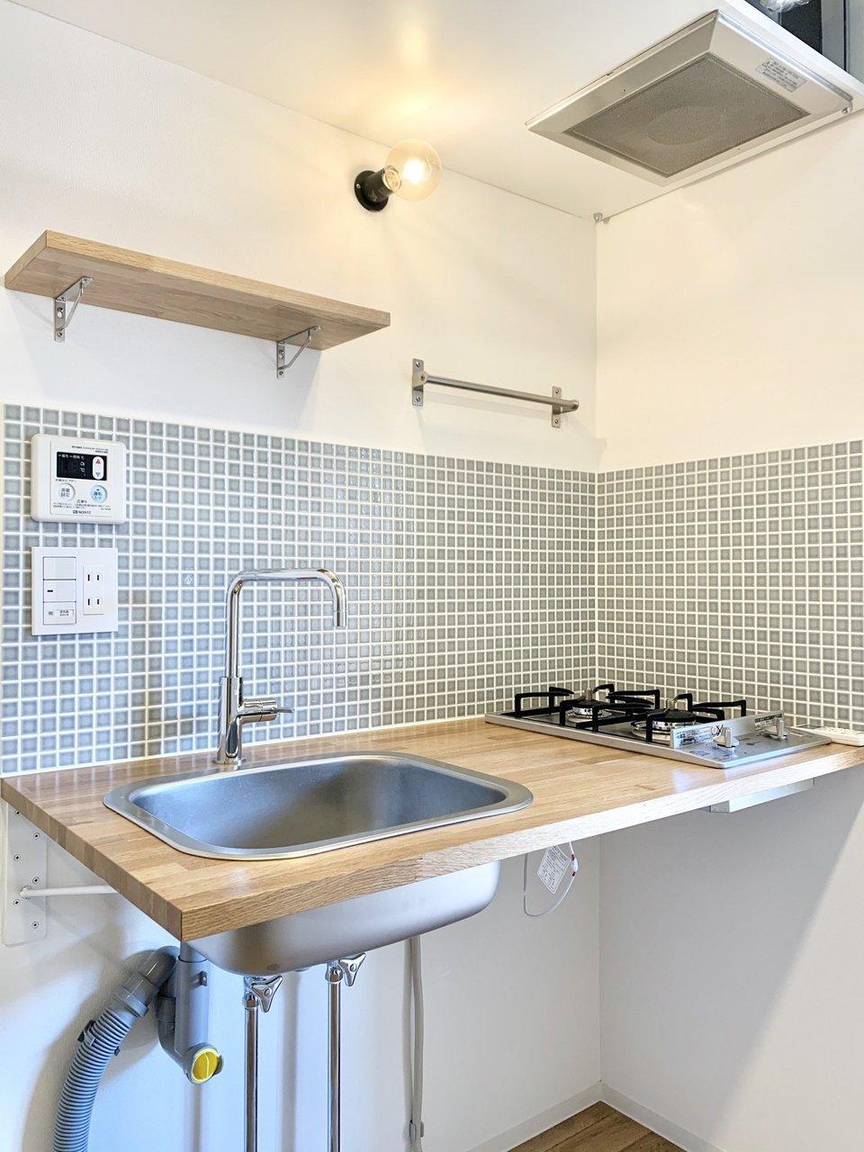 キッチン周りもとってもおしゃれ。こちらは天板も無垢材を使用しています。グリーンのタイル、ステンレスのコンロ、どこを切り取っても絵になります。