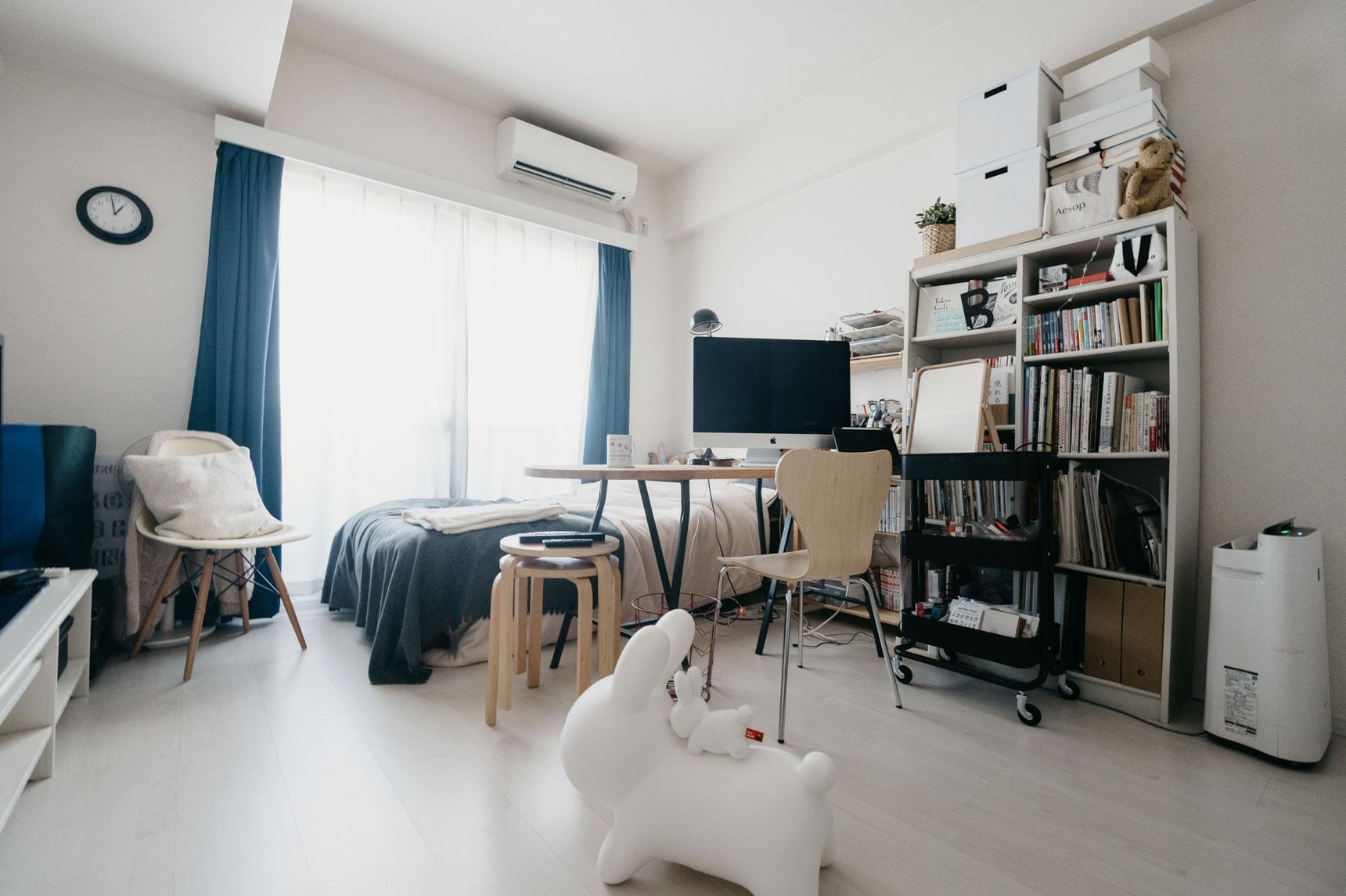 9畳1Kにお住まいの方の事例。部屋の奥にベッド、その手前にダイニングテーブルを兼ねた横長のワークデスクを配置。