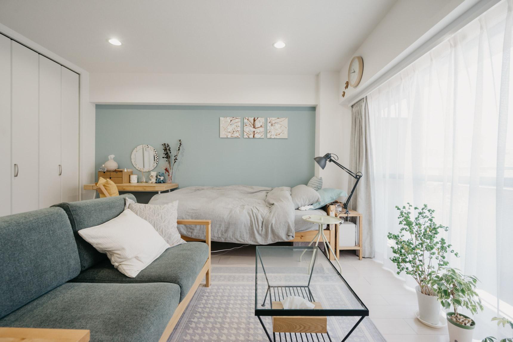 貼ってはがせる壁紙で、お部屋の一部を大人っぽいブルーグレーにされた事例。ソファやベッドリネンの色味もそれに合わせて配色し、居心地の良い北欧風のワンルームに仕上げています。(このお部屋はこちら)