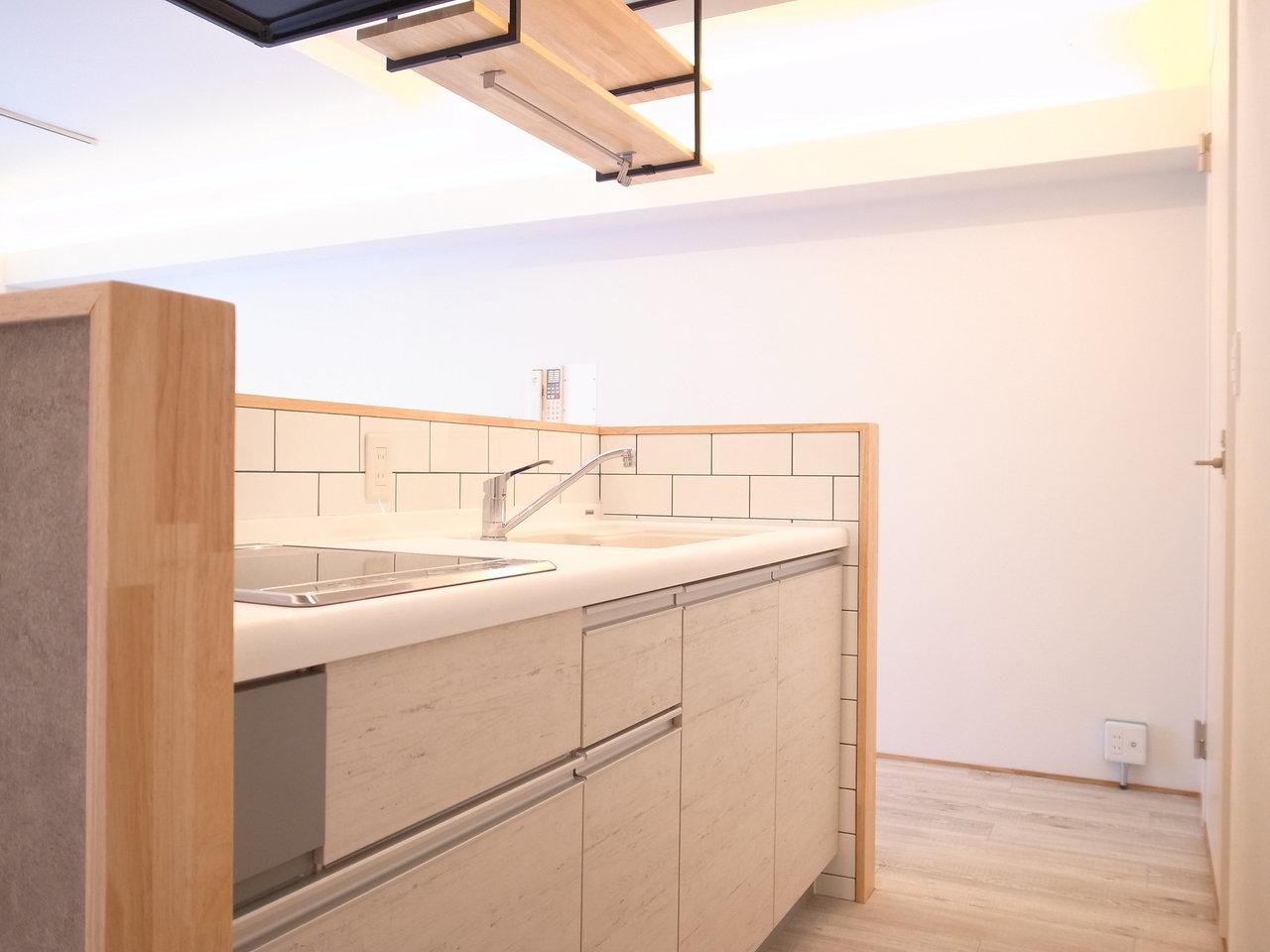 中は白を基調としたおしゃれなデザイン。シンクはとっても広めで、白いタイルのような壁面も素敵ですね。吊り棚には好きな食器やグラスを置いて、インテリアの一部にしてもいいですね。