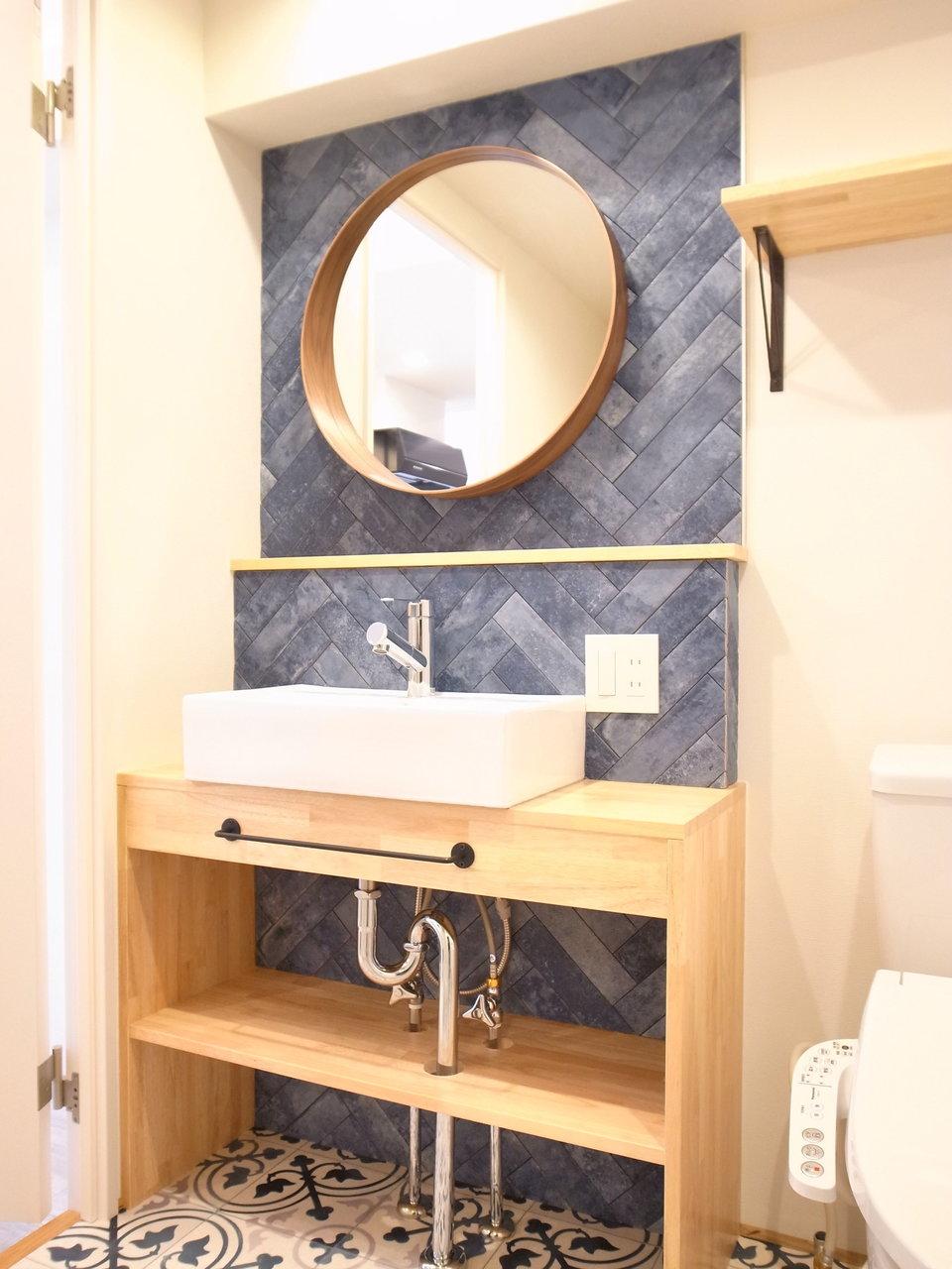 丸い鏡と木目が温かみを出している洗面台。床面のシートもおしゃれなデザインになっています。