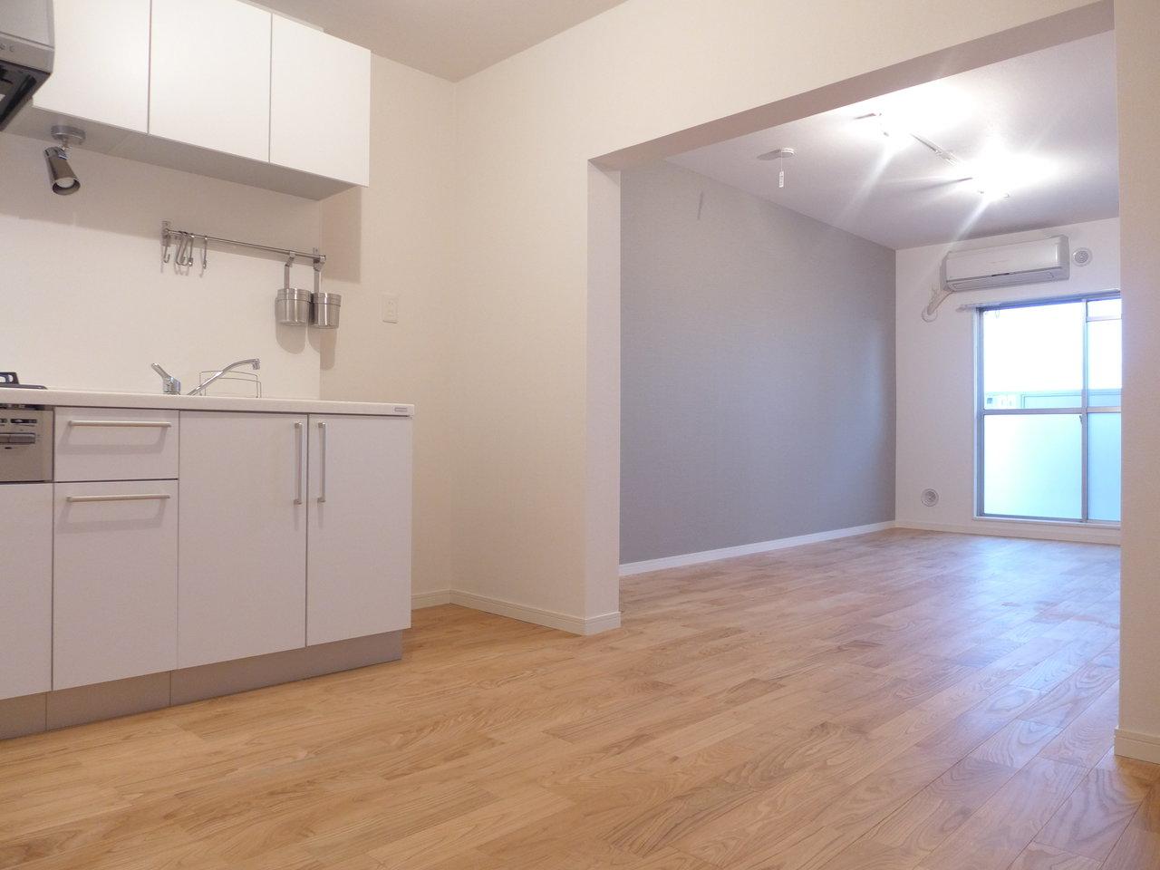 キッチンスペースとリビングはつながっていて、12畳あります。広々としていますね。グレーのアクセントクロスも落ち着きがあります。