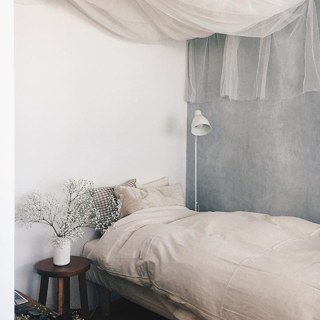 無垢床のフローリングに差し込む光が好きで決めたという、リノベーション賃貸に住んでいる方の事例。淡いグレーの壁紙をあえて貼って暮らしています。