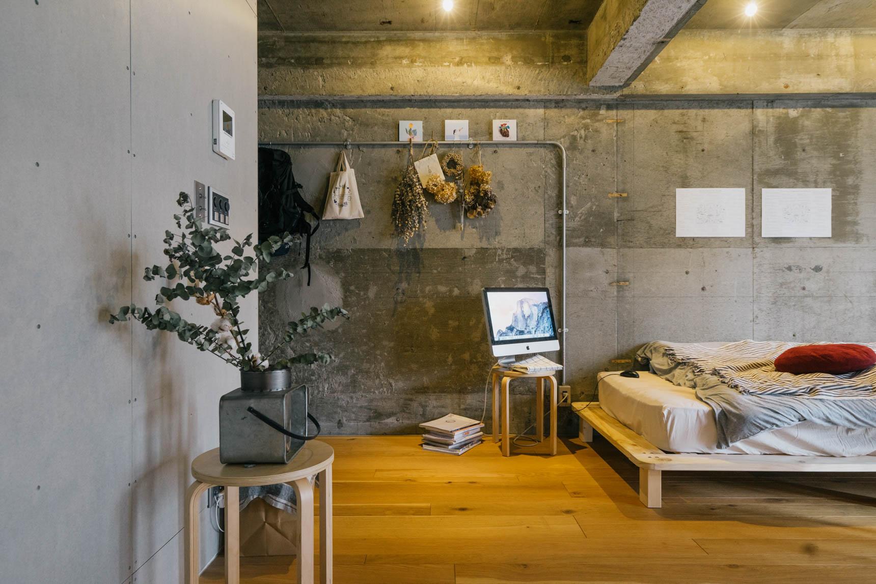 床の材質に合わせて木のスツールやベッドフレームなどを取り入れることによって、部屋全体がクールさだけでなく、温かみも生まれています。