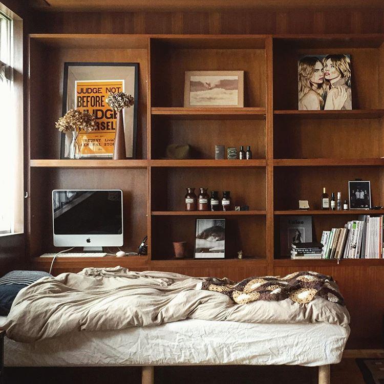 こちらは、メゾネット上階に位置する寝室。ここにも壁一面の棚があって、素敵に使われています。