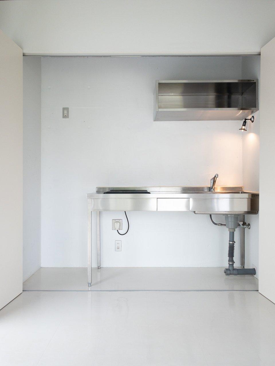 ステンレスのキッチン周り。IH2口コンロで作業スペースもあるので、十分調理はしやすそう。引き戸がついているので、生活感を出したくない方は安心ですね。